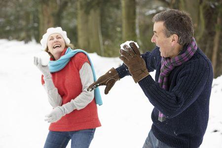 boule de neige: Couple senior ayant Snowball Fight dans la neige des bois