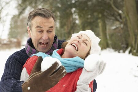 bolas de nieve: Senior pareja tener Snowball lucha contra en Woodland Snowy Foto de archivo