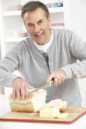 Senior Man Slicing Bread In Kitchen photo