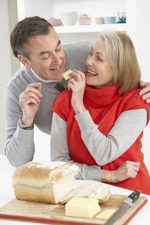 Senior Couple Making Sandwich In Kitchen photo