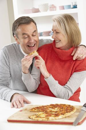 Senior Couple Sharing Takeaway Pizza In Kitchen photo