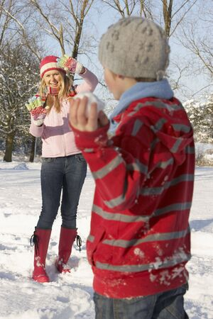 Mother And Son Having Snowball Fight In Snowy Landscape photo