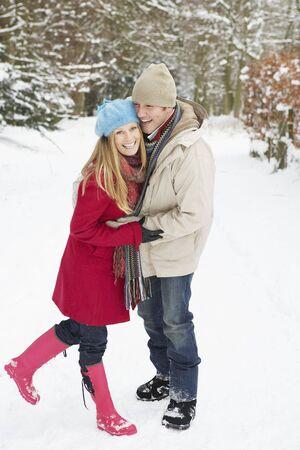 Couple Walking Through Snowy Woodland photo