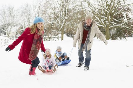Family Pulling Sledge Through Snowy Landscape photo