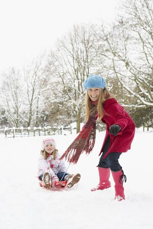 sledging people: Mother Pulling Daughter On Sledge Through Snowy Landscape