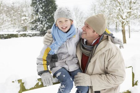 Father And Son Standing Outside In Snowy Landscape photo