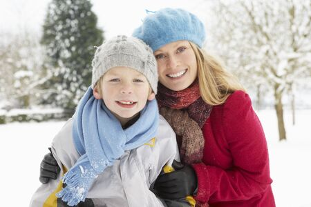 Mother And Son Standing Outside In Snowy Landscape photo