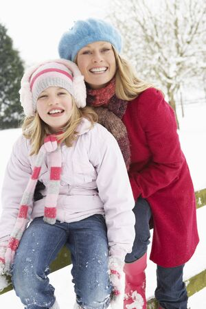Mother And Daughter Standing Outside In Snowy Landscape photo