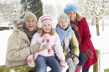 Family Sitting In Snowy Landscape photo