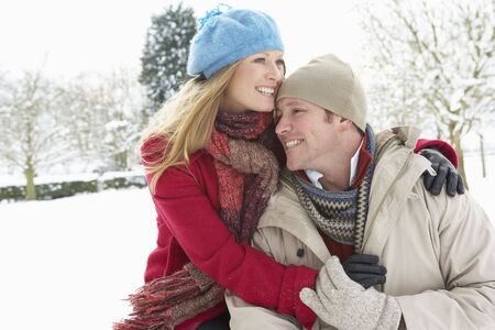 countryside loving: Couple Standing Outside In Snowy Landscape Stock Photo