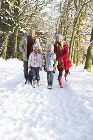 Family Walking Through Snowy Woodland photo