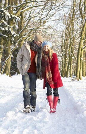 man woman hugging: Couple Walking Through Snowy Woodland