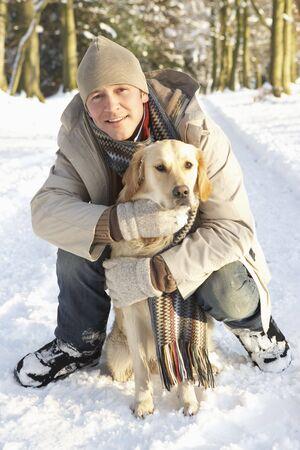 Man Walking Dog Through Snowy Woodland Stock Photo - 6451555