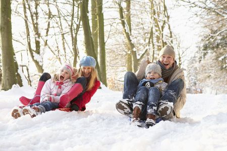 6 7 year old: Family Sledging Through Snowy Woodland
