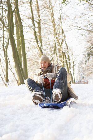 sledging: Uomo slitta attraverso il bosco innevato