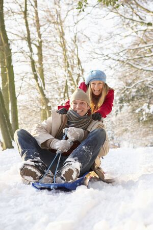 Couple Sledging Through Snowy Woodland photo