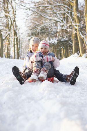 sledging: Ragazzo e ragazza slittino attraverso boschi innevati