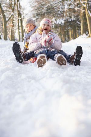 6 7 year old: Boy And Girl Sledging Through Snowy Woodland