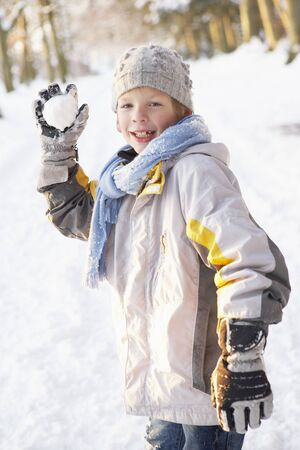Boy About To Throw Snowball In Snowy Woodland photo