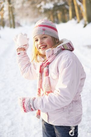 mischievious: Girl About To Throw Snowball In Snowy Woodland