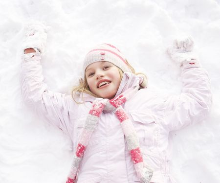 snow on the ground: Girl Laying On Ground Making Snow Angel