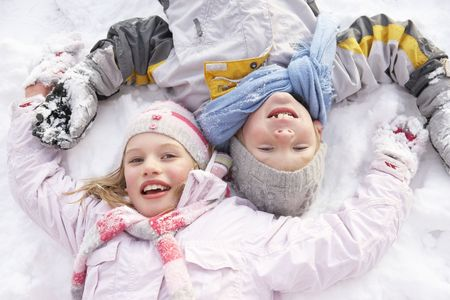Children Laying On Ground Making Snow Angel photo