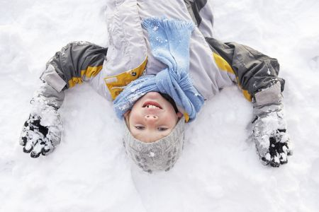 7 year old boys: Boy Laying On Ground Making Snow Angel