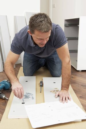 Man Assembling Flat Pack Furniture photo