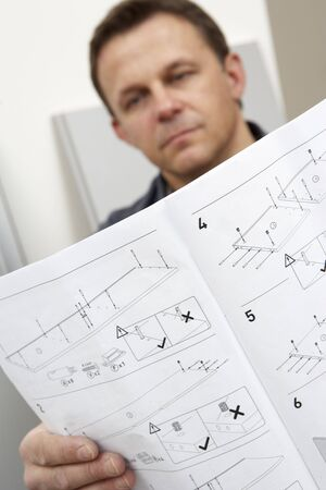 Man Reading Assembly Instructions For Flat Pack Furniture photo