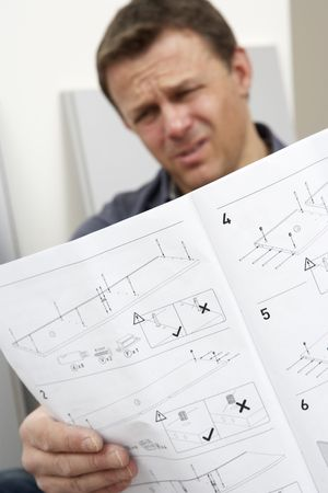 manuals: Puzzled Man Reading Assembly Instructions For Flat Pack Furniture Stock Photo