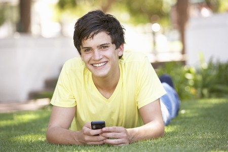 Teenage Boy Laying In Park Using Mobile Phone Stock Photo - 8108549