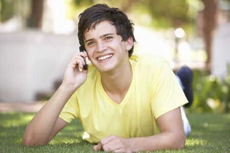 teenage boy: Teenage Boy Laying In Park Using Mobile Phone