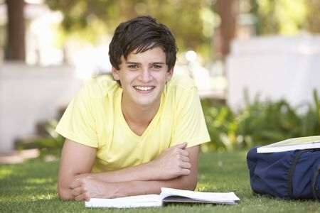 Male Teenage Student Studying In Park photo