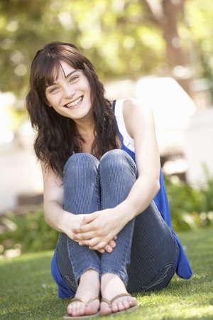 Portrait Of  Teenage Girl Sitting In Park photo