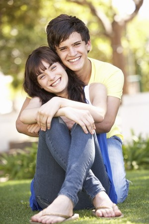 cuddling: Portrait Of  Romantic Teenage Couple Sitting In Park Stock Photo