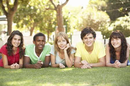 Group Of Teenagers Lying On Stomachs In Park photo