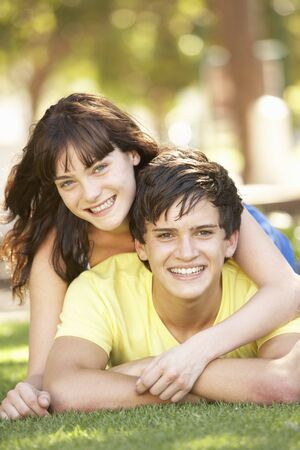 Portrait Of  Romantic Teenage Couple Sitting In Park Banque d'images
