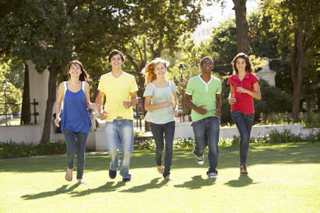 Group Of Teenagers Running Through Park photo