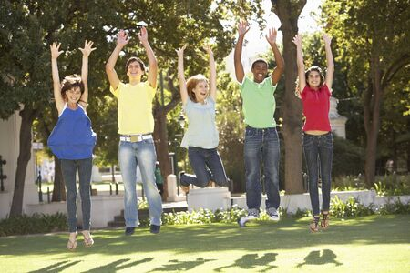 Group Of Teenagers Jumping In Air In Park photo