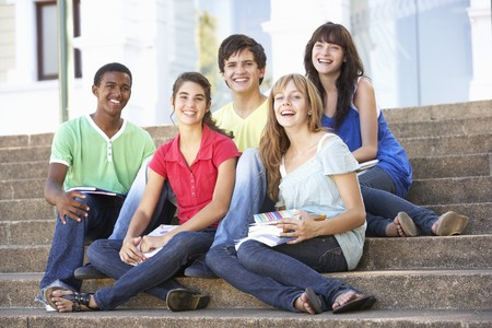 Group Of Teenage Friends Sitting On College Steps Outside photo