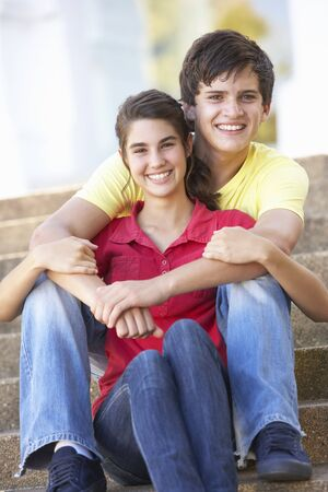 Teenage Couple Sitting On College Steps Outside photo