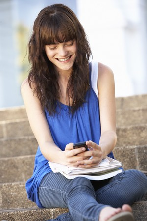 Teenage Student Sitting Outside On College Steps Using Mobile Phone Stock Photo - 8108647