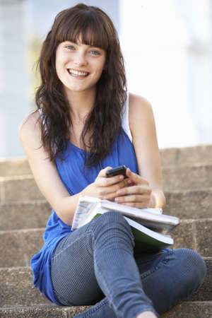 Teenage Student Sitting Outside On College Steps Using Mobile Phone photo