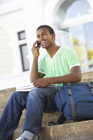 Male Teenage Student Sitting Outside On College Steps photo
