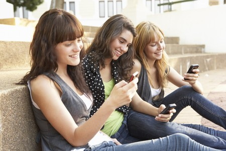 sms text: Group Of Teenage Students Sitting Outside On College Steps Using Mobile Phone