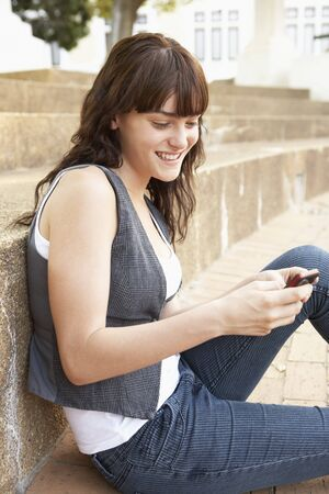 Teenage Student Sitting Outside On College Steps Using Mobile Phone Stock Photo - 8108739