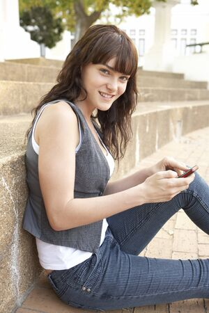 Teenage Student Sitting Outside On College Steps Using Mobile Phone Stock Photo - 8108741