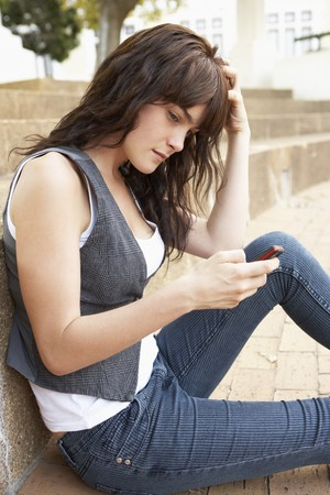 Unhappy Female Teenage Student Sitting Outside On College Steps Using Mobile Phone Stock Photo - 8108740