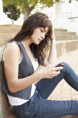 Unhappy Female Teenage Student Sitting Outside On College Steps Using Mobile Phone photo