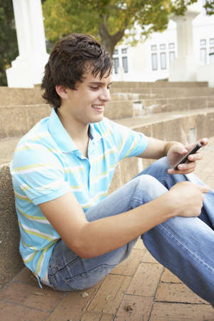Male Teenage Student Sitting Outside On College Steps Using Mobile Phone Stock Photo - 8108712